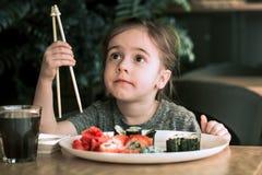 小女孩吃着寿司 免版税库存照片