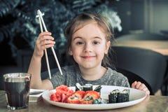 小女孩吃着寿司 免版税库存图片