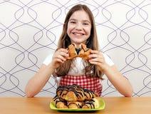 小女孩吃鲜美新月形面包用巧克力 免版税图库摄影