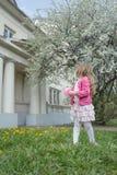 小女孩后面看法画象经典门廓的和果树在盛开背景中从事园艺 免版税库存照片