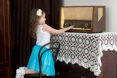小女孩听到老收音机 免版税库存图片