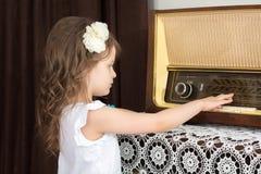 小女孩听到老收音机 图库摄影