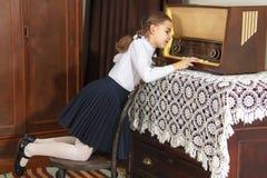 小女孩听到老收音机 免版税图库摄影