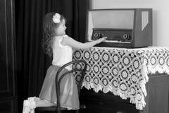小女孩听到老收音机 库存照片
