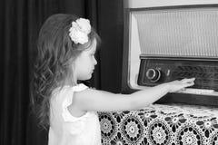 小女孩听到老收音机 免版税库存照片