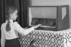 小女孩听到老收音机 库存图片
