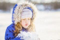 小女孩吹与手套的雪,在雪花bokeh backg 图库摄影