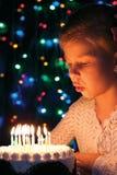 女孩吹灭在蛋糕的蜡烛 免版税库存照片