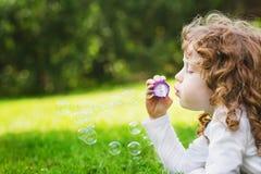 小女孩吹的肥皂泡,特写镜头画象美丽的杂种狗 免版税库存图片