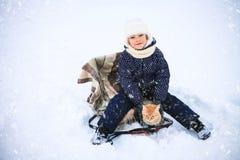 小女孩和一只红色猫在雪橇 库存图片