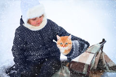 小女孩和一只红色猫在雪橇 免版税图库摄影