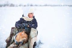 小女孩和一只红色猫在雪橇 免版税库存图片
