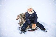 小女孩和一只红色猫在雪橇 免版税库存照片