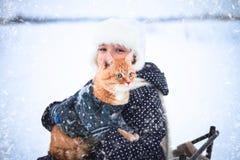 小女孩和一只红色猫在雪橇 库存照片
