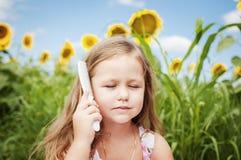 小女孩和向日葵在一个夏天晴天 喜欢您的头发 免版税图库摄影