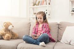 小女孩和听到音乐的玩具熊 免版税库存图片