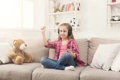 小女孩和听到音乐的玩具熊 库存图片