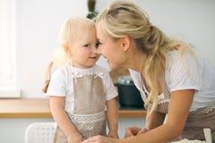 小女孩和她白肤金发的妈妈笑红色的围裙的使用和,当揉面团在厨房里时 Homemad 库存照片