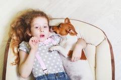 小女孩和她的小狗耳语 免版税库存照片