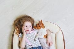 小女孩和她的小狗耳语 免版税图库摄影