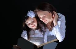 小女孩和她的母亲读了一个有趣的童话 查出在黑色背景 免版税库存照片