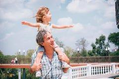 小女孩和她的父亲户外的 免版税库存照片