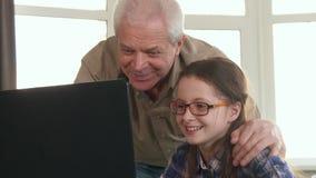 小女孩和她的祖父有在膝上型计算机的录影闲谈 图库摄影