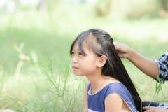 小女孩和她的mother& x27; s手安排头发 免版税图库摄影