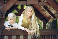 小女孩和弟弟看一个小玩具房子的窗口 免版税库存图片