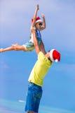 小女孩和愉快的爸爸圣诞老人帽子的享用 免版税库存图片