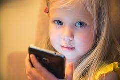 小女孩和智能手机 库存图片