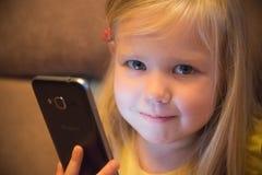 小女孩和智能手机 免版税库存图片