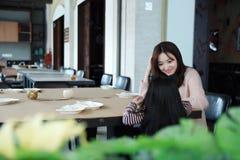小女孩和母亲坐在旅馆桌上并且等待晚餐 免版税图库摄影