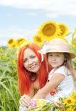 小女孩和母亲用向日葵在一个夏日 免版税库存图片