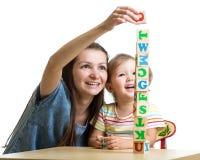 小女孩和母亲获得演奏立方体玩具的乐趣 免版税库存图片