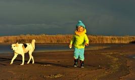 小女孩和狗在日落含沙海岸 图库摄影