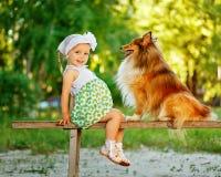 小女孩和狗坐长凳 库存照片