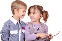 小女孩和男孩使用与片剂个人计算机 库存图片