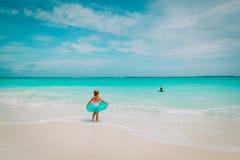 小女孩和男孩去在海滩的游泳 库存照片