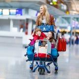 小女孩和男孩和年轻母亲带着手提箱在机场 免版税库存图片
