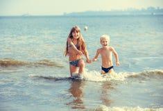 小女孩和男孩在海 库存图片