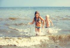 小女孩和男孩在海 免版税库存照片