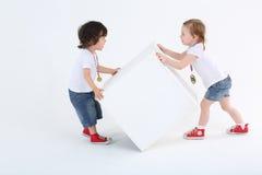 小女孩和男孩有奖牌的扭转大白色立方体 免版税库存照片