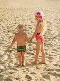 小女孩和男孩沿海滩走,握手 免版税图库摄影