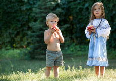 小女孩和男孩用苹果 库存照片