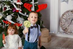 小女孩和男孩驯鹿鹿角吃的棒棒糖 免版税库存照片