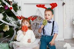 小女孩和男孩驯鹿鹿角吃的棒棒糖 库存图片