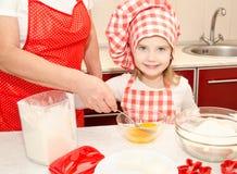 小女孩和祖母stirrring的曲奇饼面团 免版税库存照片