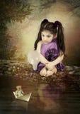 小女孩和纸小船 免版税图库摄影