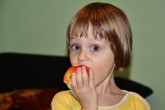 小女孩咬住红色苹果计算机 免版税库存图片